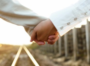 Couple Holding Hands on a Railroad Track