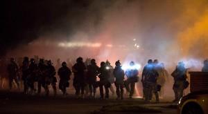 Riot police clear demonstrators from a street in Ferguson