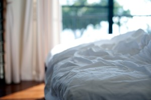 Unmade bed with white bed linen